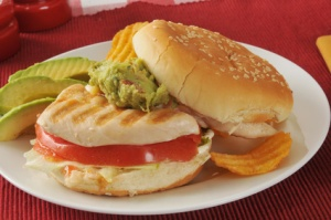 A grilled chicken sandwich with avocado slices